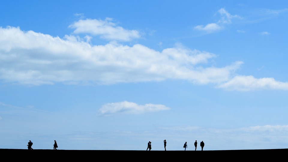 Silhouette of people walk on The Cobb  in Lyme Regis, Dorset