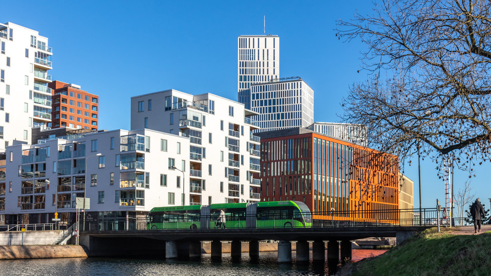 A green bus driving across a bridge over water, lots of tall building in back. Malmö Sweden